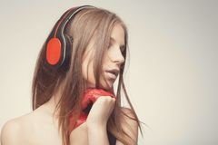 Fashion pretty girl listening music with headphones, wearing red gloves, take pleasure with song. Lifestyle woman concept. Fashion pretty girl listening music royalty free stock photo