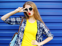 Fashion pretty girl wearing a colorful clothes having fun over blue. Background Stock Photos