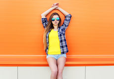 Fashion pretty girl wearing a sunglasses and shorts in city over colorful Stock Photo