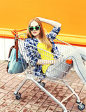 Fashion pretty girl wearing a sunglasses sitting in shopping trolley cart Stock Photos