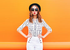 Fashion pretty glamour woman wearing a black hat sunglasses white pants over colorful orange Royalty Free Stock Photo