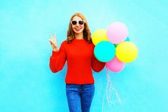 Fashion pretty laughs woman holds a colorful air balloons. On a blue background Royalty Free Stock Images