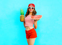 Fashion pretty slim smiling woman is holding a pineapple and a slice of watermelon. Over a colorful blue background wearing a red baseball cap Royalty Free Stock Photo