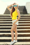 Fashion pretty slim young girl wearing a sunglasses, t-shirt and shorts Royalty Free Stock Images