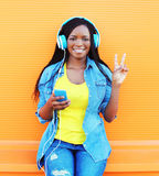 Fashion pretty smiling african woman in a headphones listens to music over orange background royalty free stock image
