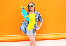 Fashion pretty smiling girl with skateboard over colorful orange Stock Photo