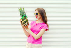 Fashion pretty smiling girl in sunglasses looking on pineapple over white Royalty Free Stock Photography