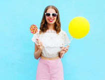 Fashion pretty smiling woman with air balloon and lollipop over colorful blue. Background Stock Photo