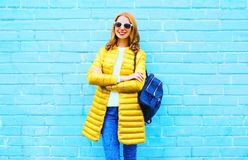 Fashion pretty smiling woman with backpack on colorful blue background. Fashion pretty smiling woman with backpack on a colorful blue brick background Royalty Free Stock Photography