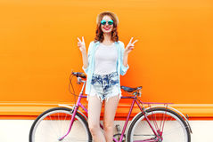 Fashion pretty smiling woman with bicycle over colorful orange Stock Photography