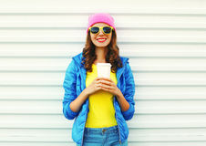 Fashion pretty smiling woman with coffee cup in colorful clothes over white background wearing a pink hat yellow sunglasses. And blue jacket Royalty Free Stock Images