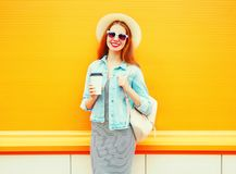 Fashion pretty smiling woman with a coffee cup on a orange. Background Stock Photos