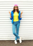 Fashion pretty smiling woman in colorful clothes posing over white background wearing pink hat yellow sunglasses and blue jacket. Fashion pretty smiling woman in Stock Photography