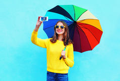 Fashion pretty smiling woman with colorful umbrella taking autumn photo makes self portrait on smartphone over blue background Stock Photography