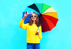 Fashion pretty smiling woman with colorful umbrella taking autumn photo makes self portrait on smartphone over blue background Stock Image