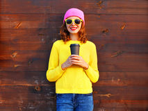 Fashion pretty smiling woman holding coffee cup in colorful clothes over wooden background wearing pink hat yellow sweater. Fashion pretty smiling woman holding Royalty Free Stock Image