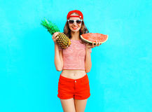 Fashion pretty smiling woman is holding a pineapple and a slice of watermelon Stock Image