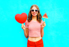 Fashion pretty smiling woman is holding a red balloon heart shape and slice watermelon ice cream Stock Image