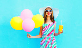 Fashion pretty smiling woman holds a fruit juice cup with an air colorful balloons. Over a blue background stock photos