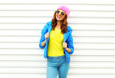 Fashion pretty smiling woman model in colorful clothes posing over white background wearing a pink hat yellow sunglasses. And blue jacket Royalty Free Stock Photography