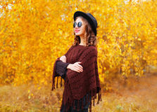 Fashion pretty smiling woman model wearing a black hat sunglasses and knitted poncho over autumn yellow leaves Stock Photo