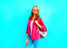 Fashion pretty smiling woman in a pink denim jacket on blue Stock Photo