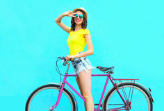 Fashion pretty smiling woman on retro pink bicycle over colorful blue Royalty Free Stock Photo