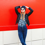 Fashion pretty smiling woman in rock black style posing over red Stock Image