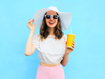 Fashion pretty smiling woman in straw hat with cup fruit juice over colorful blue. Background Stock Photo