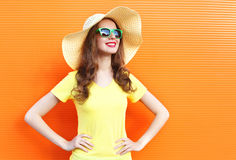 Fashion pretty smiling woman in sunglasses and straw hat over colorful. Orange background Royalty Free Stock Photos