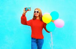 Fashion pretty smiling woman takes a picture self portrait on a. Smartphone with an air balloons Stock Photography