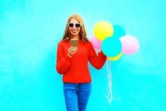 Fashion pretty smiling woman is using smartphone with an air balloons. On a blue background Stock Image