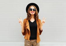 Fashion pretty smiling woman wearing a black hat, sunglasses and jacket over urban background. Fashion pretty smiling woman wearing a black hat, sunglasses and Royalty Free Stock Photo