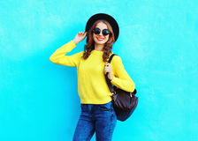 Fashion pretty smiling woman wearing a black hat yellow knitted sweater and backpack over colorful blue. Background Stock Images