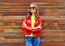 Fashion pretty smiling woman wearing red leather jacket in autumn over wooden background. Fashion pretty smiling woman wearing a red leather jacket in autumn Stock Photo