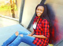Fashion pretty smiling young african woman wearing a red checkered shirt sitting. In the city Royalty Free Stock Photos