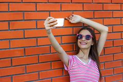 Fashion pretty smiling young girl taking picture self portrait on smartphone in striped t-shirt over city red brick background.  Royalty Free Stock Image