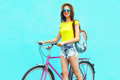 Fashion pretty smiling young woman with bicycle over colorful blue background in summer Royalty Free Stock Photo