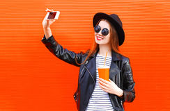 Fashion pretty smiling young woman taking picture self portrait on smartphone in black rock style over city red Stock Photo