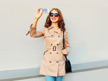 Fashion pretty smiling young woman taking picture self portrait on smartphone wearing a coat black handbag clutch in city Stock Image