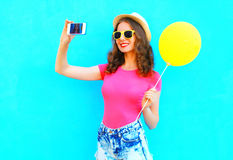 Fashion pretty smiling young woman taking picture self portrait on smartphone with yellow air balloon wearing a pink t-shirt Royalty Free Stock Photos