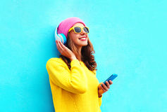 Fashion pretty sweet carefree girl listening to music in headphones with smartphone wearing a colorful pink hat yellow sunglasses. Sweater over blue background