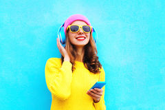 Fashion pretty sweet carefree girl listening to music in headphones with smartphone wearing colorful pink hat yellow sunglasses. Sweater over blue background Royalty Free Stock Photos