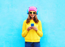 Fashion pretty sweet carefree woman listening music in headphones browsing smartphone wearing colorful pink hat yellow sunglasses Stock Photography