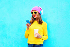 Fashion pretty sweet carefree woman listening music in headphones browsing using smartphone wearing colorful Stock Photo