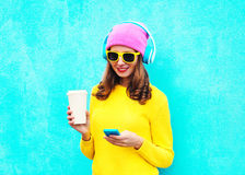 Fashion pretty sweet carefree woman listening music in headphones browsing using smartphone wearing a colorful pink hat Royalty Free Stock Image