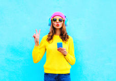 Fashion pretty sweet carefree woman listening music in headphones with smartphone wearing a colorful pink hat yellow sweater Royalty Free Stock Images