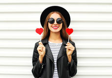 Fashion pretty sweet young smiling woman with red lips holds lollipop heart wearing black hat leather jacket over white Royalty Free Stock Images