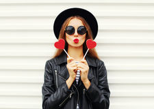 Fashion pretty sweet young woman with red lips making air kiss with lollipop heart wearing black hat leather jacket over white Royalty Free Stock Photos