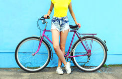 Fashion pretty woman and bicycle over colorful blue backgroun Royalty Free Stock Photo